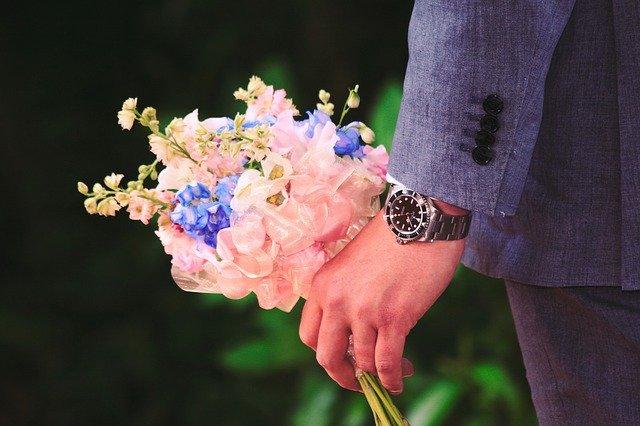時計を付けた男性の手に花束